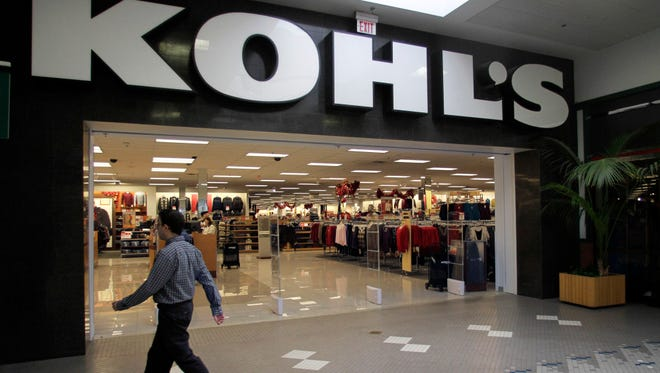 A passerby walks near the entrance of a Kohl's department store in Walpole, Mass.