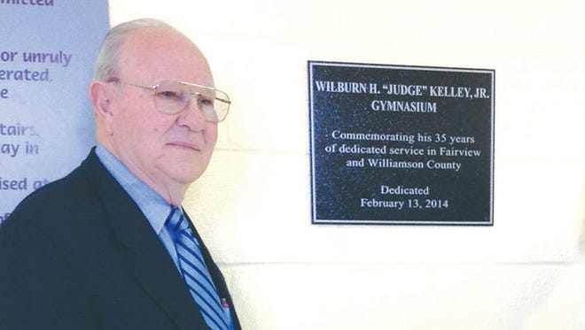Wilburn Kelley, Jr. proudly stand beside the wall plaque naming the Fairview Recreation Center gymnasium in his honor in February 2014.