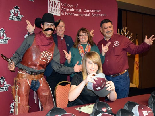 Emma McDonald, of Cliff, N.M., puts on a cap after signing a certificate of commitment during an ACES Aggie Signing Day ceremony. Posing in the photo are Pistol Pete, College of Agricultural, Consumer and Environmental Sciences assistant dean Jerry Hawkes, Kristin Chavez and Anthony Chavez, president of the Sam Steel Society advisory council.