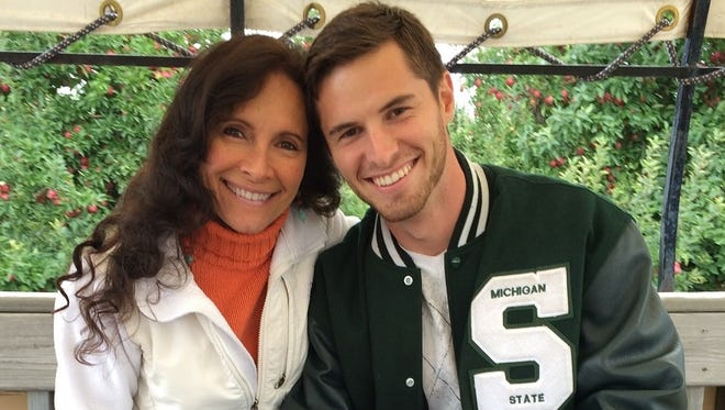 "Former MSU punter Mike Sadler sits with his mother, Karen. Karen called her son her ""best friend."""