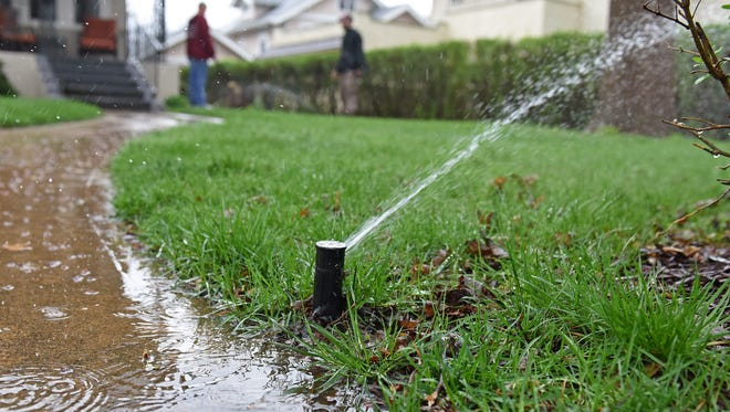 Eric Blair and Kenny Lomheim, with Lipetzky's Irrigation and Landscape, check on the sprinkler system at a home in the McKennan Park neighborhood on Monday.