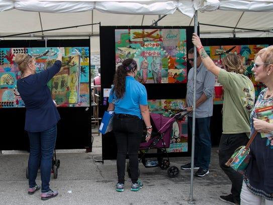 Ginger Ott, left, admires her artwork purchased at