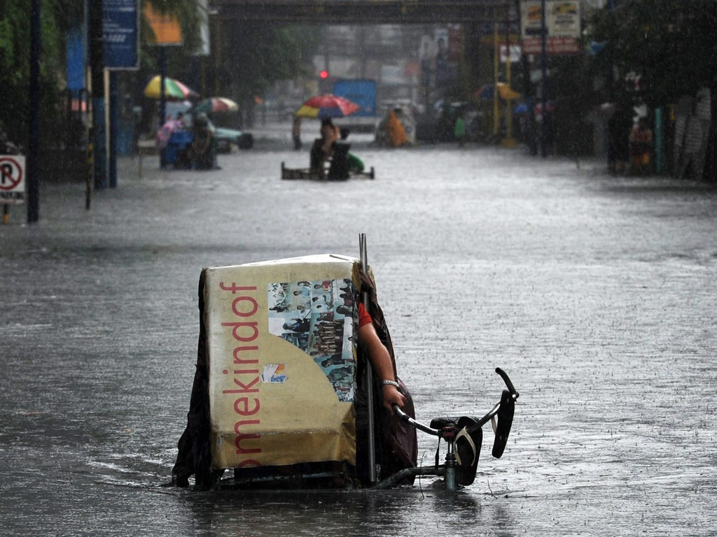 A resident riding a tricycle negotiates floodwaters after a sudden heavy downpour inundated streets in the financial district of Manila.