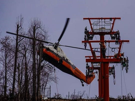 A helicopter lifts parts for rebuilding the Gatlinburg