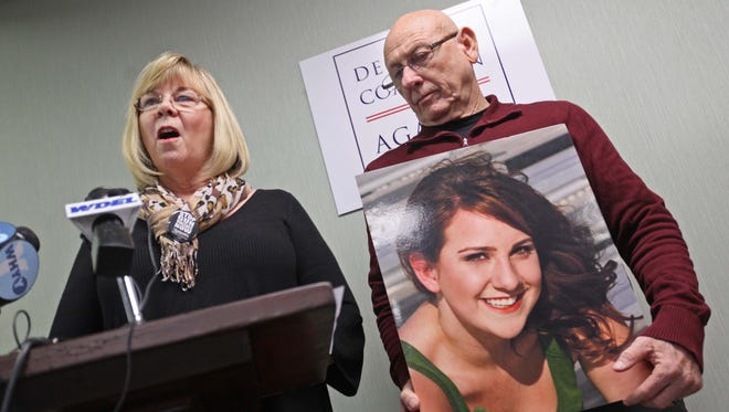 Sandy Phillips, mother of 24-year-old Jessica Redfield Ghawi killed July 20, 2012 during the movie theater shooting in Aurora, Colo., speaks Jan. 9, 2014, at a press conference with her husband, Lonnie, who is holding their daughter's picture.