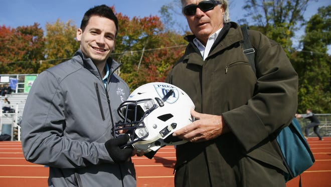 Dr. Dante Marconi (left) and Dr. Vincent Vigorita with Mater Dei helmet used in concussion study during high school football game at Mater Dei Prep Oct. 29.