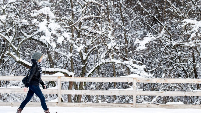 Chloe McLennan walks down a snow-covered path at Shelby Park on Saturday in Nashville.