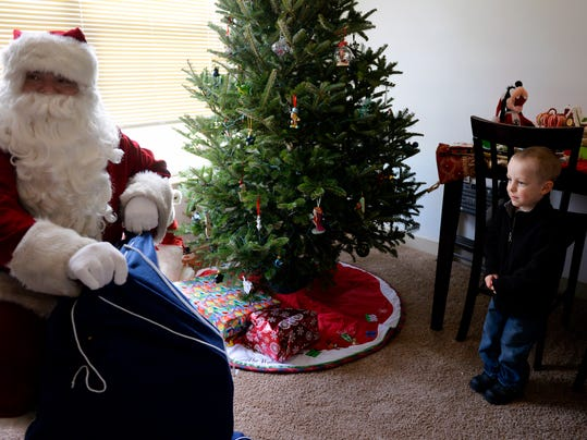 Santa Claus, played by Elmer Baker, opens up his bag in veteran Ryan Walton's York Township living room as Walton's son Ayden, 3, watches shyly on Saturday, Dec. 21, 2013. With the help of Santa and Mrs. Claus, CJ Hoffman and her nonprofit Feed the Vets Red Lion delivered an early round of Christmas presents, grocery gift cards and food to York Township veteran Ryan Walton's family on Saturday, Dec. 21, 2013. Walton, who served in Iraq and was at Fort Hood at the time of the 2009 shooting, is currently hospitalized for renal failure and disintegrating spinal discs. Chris Dunn -- Daily Record/Sunday News