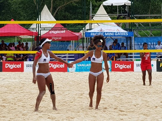 Team Guam's Tatiana Sablan, left and Kendra Byrd slap hands after a successful play in their match against Kiribati at the X Pacific Mini Games in Port VIla, Vanuatu on Wednesday.