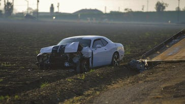 A Dodge Challenger involved in the Visalia Unified bus crash sits in a field on Tuesday afternoon.