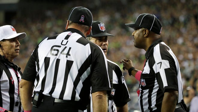 Officials, including side judge Keith Washington, right, discuss a play late in the fourth quarter of Monday night's game between the Seattle Seahawks and the Detroit Lions in Seattle. It was ruled a touchback after Lions wide receiver Calvin Johnson fumbled and the ball went out of bounds in the end zone.