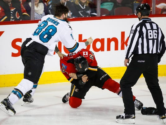 San Jose Sharks' Brent Burns, left, fights with Calgary Flames' Garnet Hathaway during second period NHL hockey action in Calgary, Alberta, Monday, March 7, 2016. (Jeff McIntosh/The Canadian Press via AP)