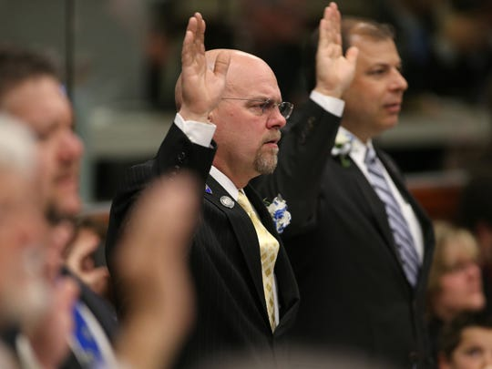 Nevada Assembly Republicans Ira Hansen of Sparks, center, and Paul Anderson of Las Vegas, right, take the oath of office in 2013.