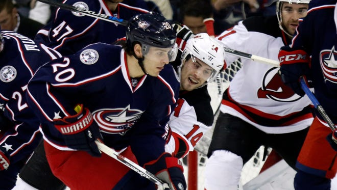 Columbus Blue Jackets' Brandon Saad, left, works for the puck against New Jersey Devils' Adam Henrique during the second period of an NHL hockey game.