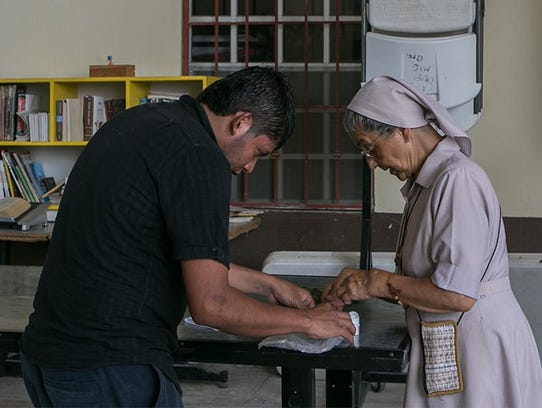 A nun helps a patient with his medication at the Our