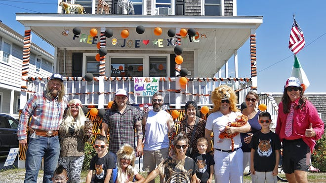 """A house decorating contest replaced the annual Scituate Beach Association Labor Day parade this year. The MacLaughlan family gathers in front of their """"Tiger King"""" themed house."""