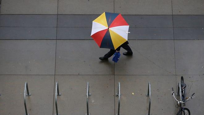 A pedestrian carries an umbrella as it rains in Sacramento on Thursday.