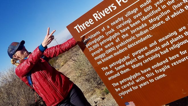 Anna Dozier checks out the Three Rivers Petroglyph Site sign while on a hike.