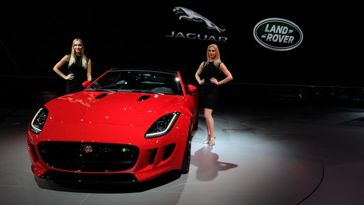 The brands with the highest rate of software complaints per 1,000 vehicles from 2011-16: Jaguar. Models stand next to a Jaguar F-Type Coupe.