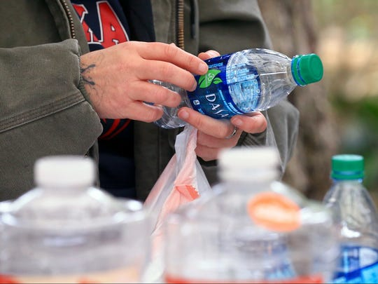 Kaitlin McComb removes plastic from a bottle as she helps work on a bottle sculpture after the Corpus Christi's recent water crisis on Saturday, Jan. 28, 2017, in Corpus Christi.