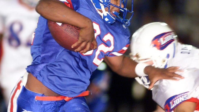 Hays running back Ty Calvin fights for more yardage against Leander during the teams' 2001 meeting. During a game in 1999, Calvin recalls a teammate threaten a Black referee with the Confederate flag that was stitched on the team's jersey at the time.