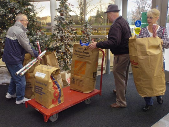 Volunteers Mike Theisan, Jim McLaughlin and Nancy Williams sort donations during a past Canton Goodfellows Christmas gift distribution.