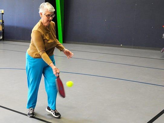 Pickleball player Joyce Curtis hits a ball against