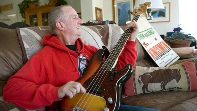 """Jack Ely, co-founder of the early 60's band The Kingsmen and best known for his 1963 rendition of the song """"Louie, Louie"""", plays his Fender bass guitar at his home in Terre Bonne, Oregon on April 16, 2009."""