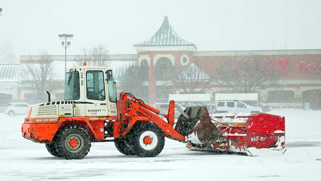 A plow truck works to remove snow at the Acme parking lot on South Main Road in Vineland.