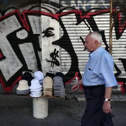 A man walks past hats for sale in front of graffiti symbols of the euro and the dollar in Athens on July 6, 2015.