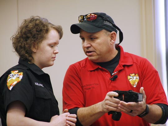 Sergeant Al Shaffer, right, teaches Alyssa Elkins, 16, how to use a Taser at the Newark Police headquarters on Sunday, Jan. 29, 2017. Elkins then used it on Newark Police Sgt. Doug Bline and later on her uncle, Ohio State Patrol Trooper Josh Barry. Police helped Elkins, a lukemia patient, cross off the bucket-list item.