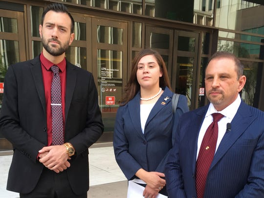 Tahnee Gonzales stands next to her attorneys Marc Victor (right) and Andrew Marcantel outside of a courthouse on March 29, 2018.