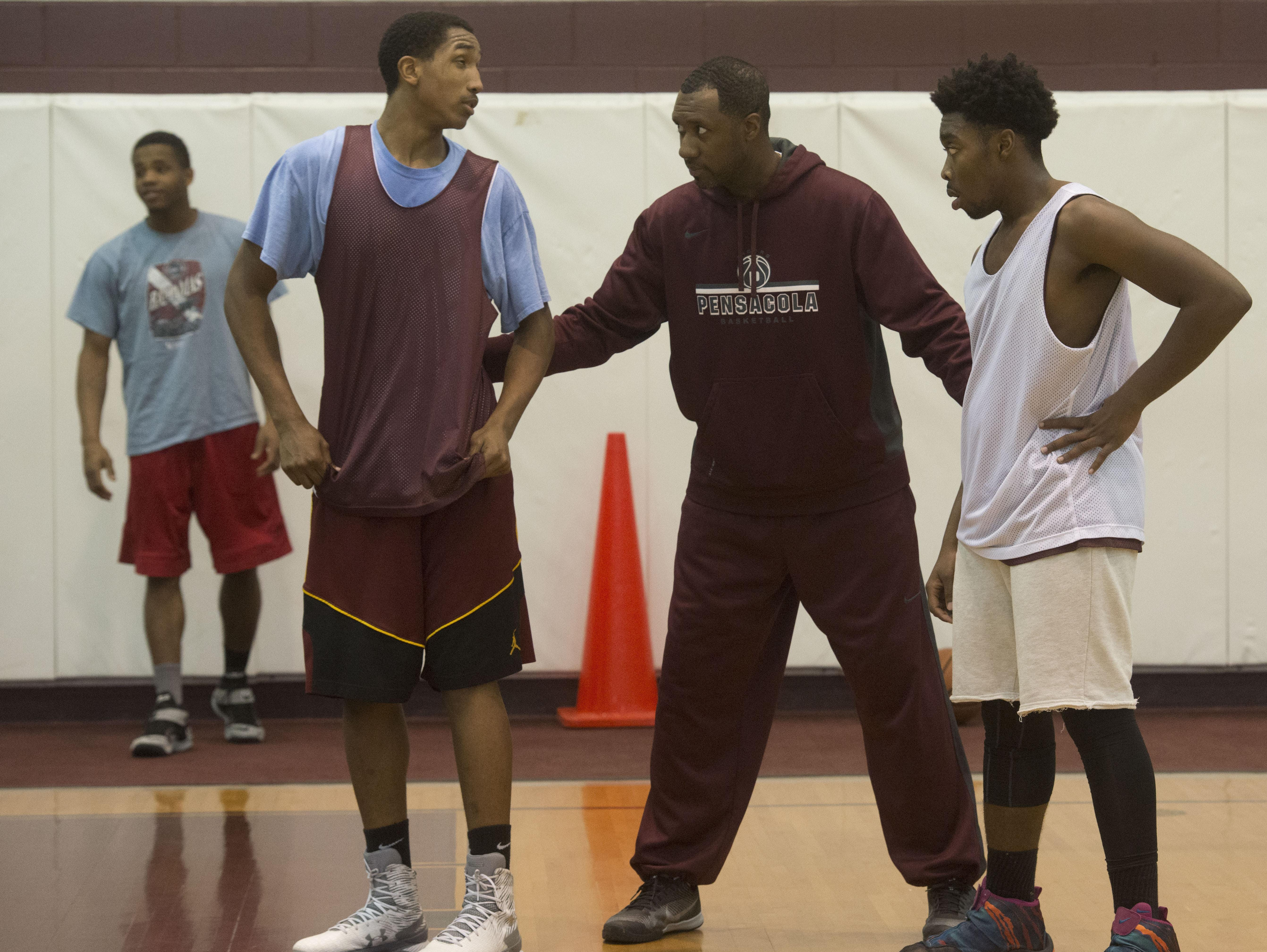 Pensacola High School Basketball Coach, Terrence Harris, center, walks players, Davonchae Bryant, left, and Javen Johnson, right, through a play during practice. The Tigers host Gainesville High on Friday at 7 p.m. in the Region 1-6A Finals.