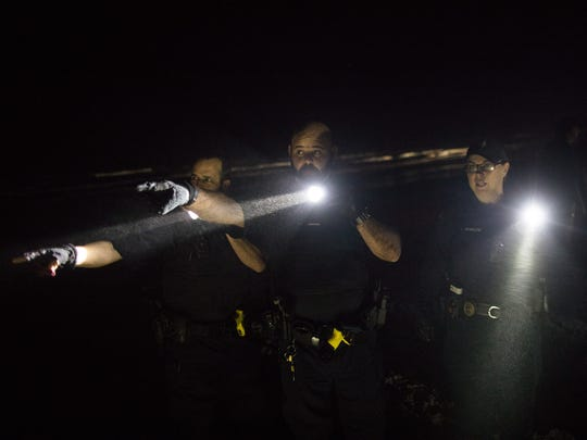 Port Aransas police officers shine their flashlights