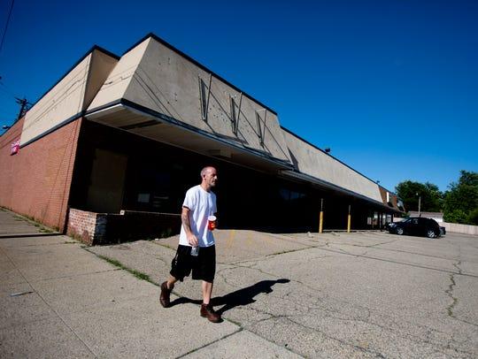 A man walks past a shopping center on Monday, June