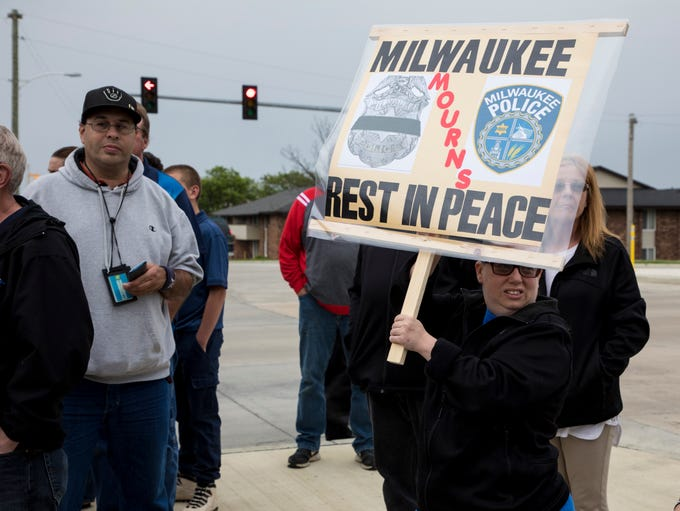 A woman holds a sign Monday at a vigil for Milwaukee