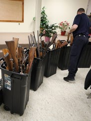 Bins of turned in long guns are pictured during the