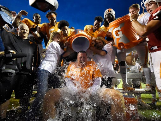 Tennessee coach Butch Jones, center, gets a cooler of ice dumped on him while participating in the Ice Bucket Challenge at the conclusion of the football team's open practice at Neyland Stadium on Saturday.
