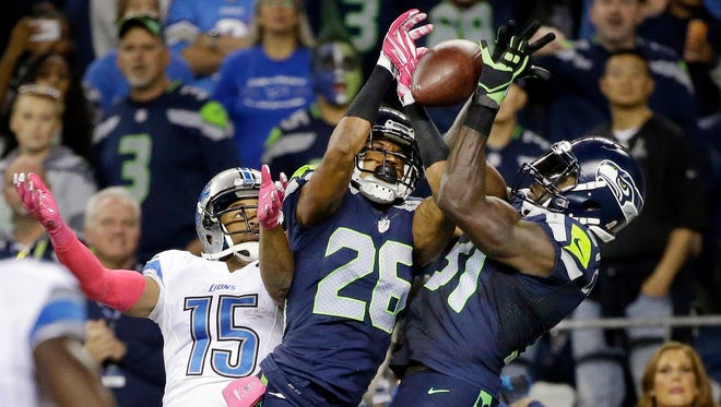 FILE - In this Oct. 5, 2015, file photo, Seattle Seahawks strong safety Kam Chancellor, right, and cornerback Cary Williams (26) break up a pass intended for Detroit Lions wide receiver Golden Tate (15) in the second half of an NFL football game, in Seattle.