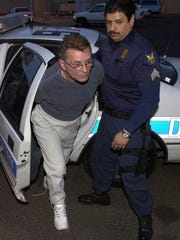 "Mafia hit man and turncoat Salvatore ""Sammy the Bull"" Gravano is escorted to jail by a Phoenix police officer on Feb. 24, 2000, after raids on a criminal syndicate dealing in the designer drug Ecstasy. Gravano was booked into Maricopa County Jail on suspicion of drug trafficking."