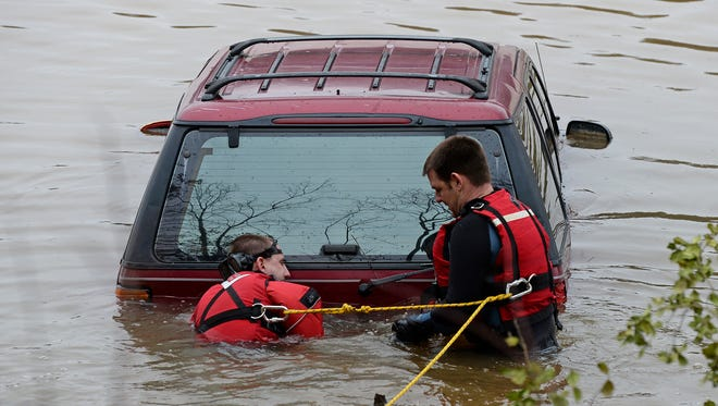 Anderson Fired Dept. rescue divers Joshua Hawkins, left, and Hunter Hartline hook a chain to an SUV that was found in the Saluda River near the Holiday Dam in Belton on Tuesday, February 23, 2016.