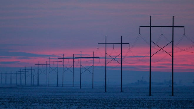 Power lines snake across a snow covered farm field in Clarks Hill, Ind.