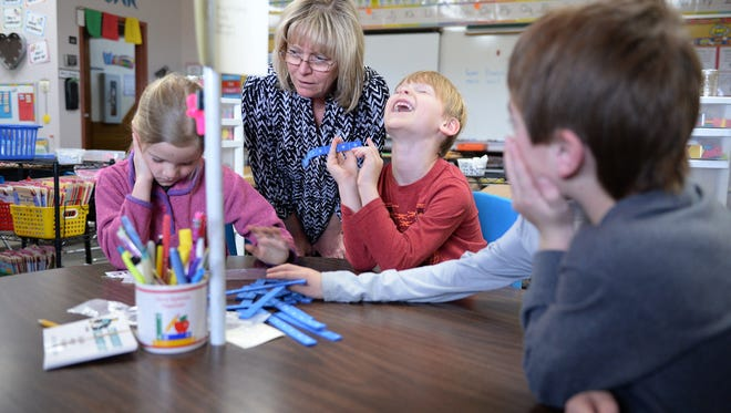 Teacher Susan Knapp works with students Nina Gates and Jameson Crowley at Stansberry Elementary in Loveland on Monday, March 6, 2017. Thompson School District's bond to build new schools wasn't approved in November. Now the district is considering closing two schools to cut costs.