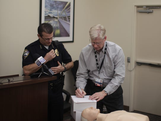 Redding Police Chief Roger Moore, left, signs for 24