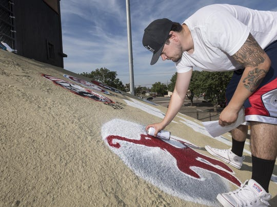Muralist A.J. Gomez paints logos of the 11 different franchises that have been associated with baseball in Visalia over the years on Wednesday, April 5, 2017. This mural is along the third base side of the stadium, another is at the other end.
