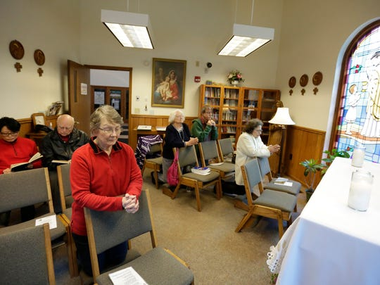 A group of parishioners pray Tuesday in the Adoration