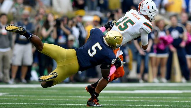 Oct 29, 2016; South Bend, IN, USA; Miami Hurricanes quarterback Brad Kaaya (15) is sacked by Notre Dame Fighting Irish linebacker Nyles Morgan (5) in the second quarter at Notre Dame Stadium. Mandatory Credit: Matt Cashore-USA TODAY Sports