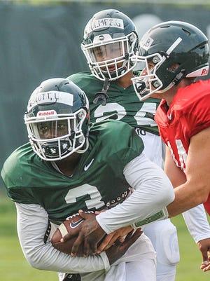 MSU running back LJ Scott takes a handoff from quarterback Brian Lewerke during practice Aug. 21, 2017.