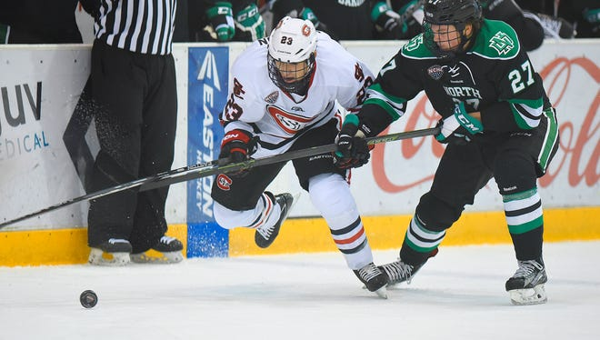Robby Jackson of St. Cloud State and North Dakota's Luke Johnson try to get control of the puck during a game at the Herb Brooks National Hockey Center in St. Cloud.
