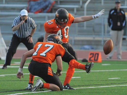 Washington's Brock Walker kicks the ball with the help